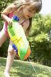 Little girl in park shooting water pistol into grass