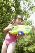 Girl in park shooting pump action water pistol