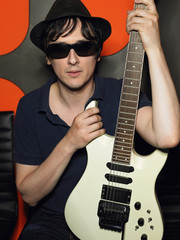 Young man in sunglasses holding guitar, portrait