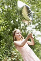 Girl in park playing in park with helium filled balloon