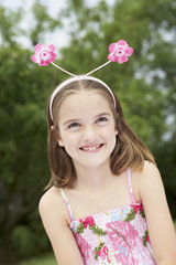 Girl in backyard Wearing Floral Deely Boppers, portrait