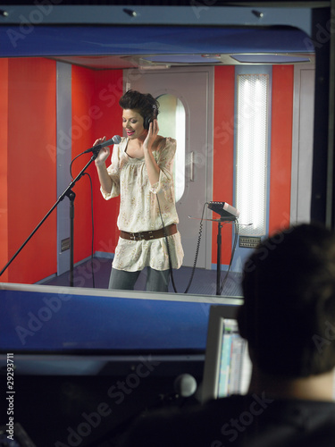 Young woman singing in studio, technician in foreground
