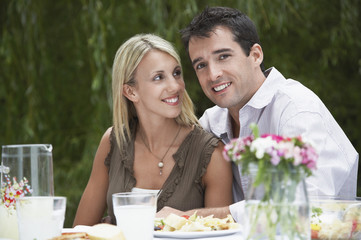 Mid-adult couple dining at table in garden