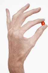 Woman holds red pill between finger and thumb