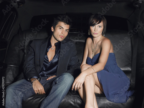 Couple in evening wear in back of limousine