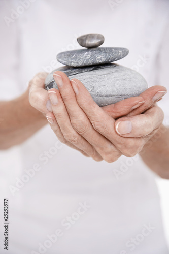 Woman Holding Pile of Stones, mid section