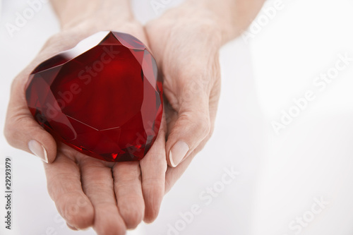 Woman showing heart-shaped jewel, close up on hands