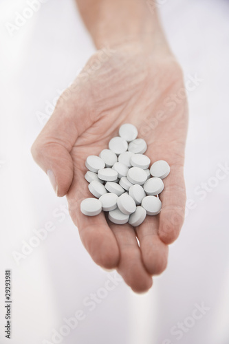 Senior woman holding out hand full of pills, close-up on hand