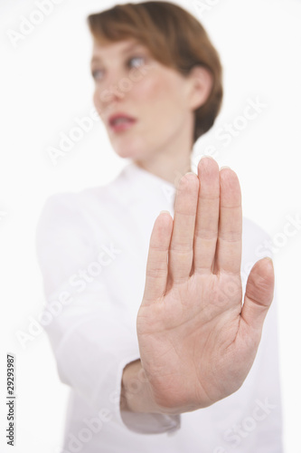 Woman holding up hand, studio shot