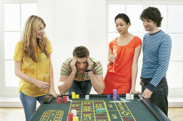 Young frustrated man at roulette table with friends
