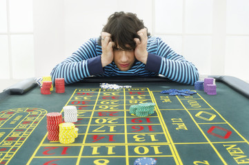 Young frustrated man at roulette table