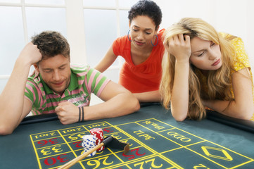 Young man at roulette table losing large bet