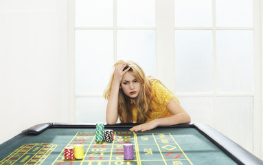 Young woman losing on roulette table