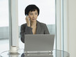 Businesswoman sitting at table with laptop, talking on phone