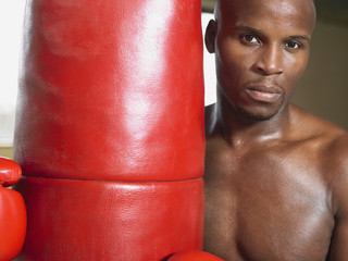 Boxer holding punching bag, portrait, close-up