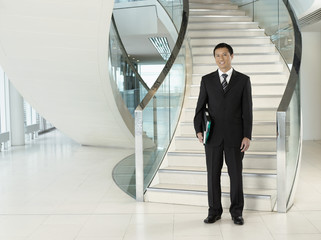 Confident Businessman, holding folder, standing in front of stairs