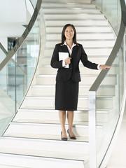 Confident Businesswomen holding folder, standing on stairs, hand on banister