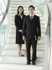 Confident Businesspeople standing on staircase