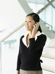 Smiling businesswoman standing, talking on mobile