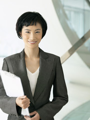 Smiling businesswoman standing, holding clipboard