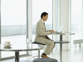 Businessman sitting at table, working on laptop, side view