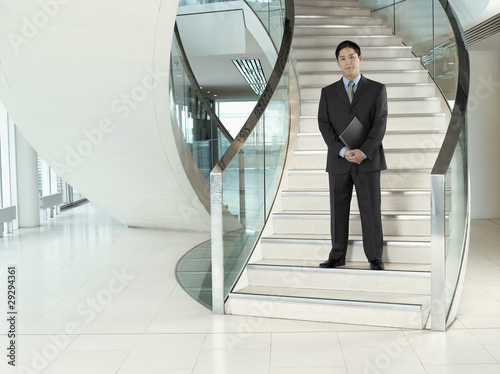 Confident Businessman, holding folder, standing on stairs