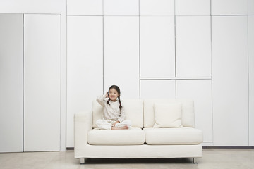 Young, barefoot Girl sitting cross-legged Sofa