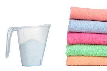 Measuring cup with detergent and a pile of colorful towels