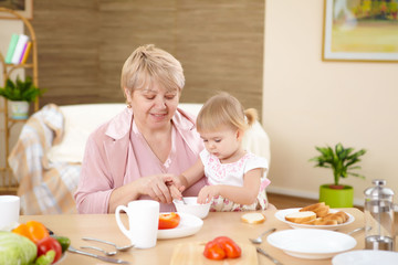 grandmother feeding granddaughter at home