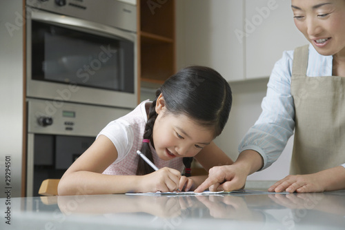 Mother standing at kitchen counter, Pointing at Daughter's Drawing