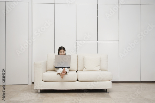 Young, barefoot Girl Using Laptop on Sofa