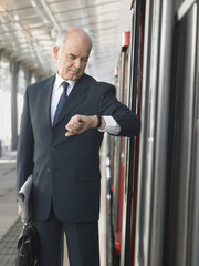 Mature Businessman checking time, standing outside train in station