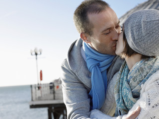 Couple kissing, standing on pier, head and shoulders
