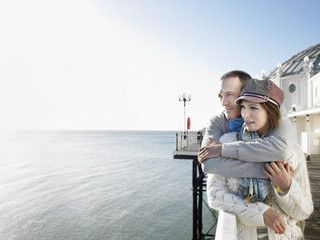 Affectionate couple, standing on pier, looking out to sea