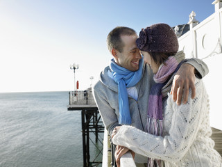 Couple laughing, standing on pier, half length