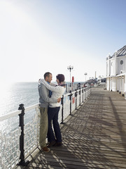 Couple embracing, standing on pier, side view, full length