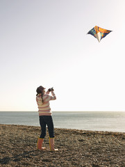 Pre teen girl flying kite on beach, full length