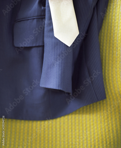 Suit and Tie on Bed with yellow cover, close-up