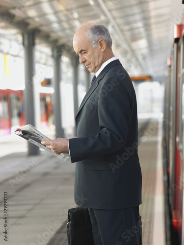 Businessman Reading Newspaper at empty Train Station, side view