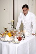 Waiter with room service breakfast table