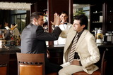 Two men slapping hands in agreement at a bar
