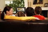 Couple watching television with young children