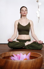 Young woman in a fitness class meditating