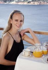 Young woman having breakfast on hotel terrace