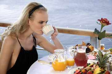 Young woman having breakfast on hotel terrace