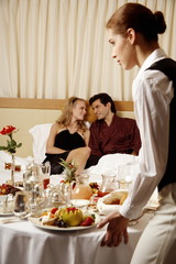 Couple having room service breakfast in hotel room
