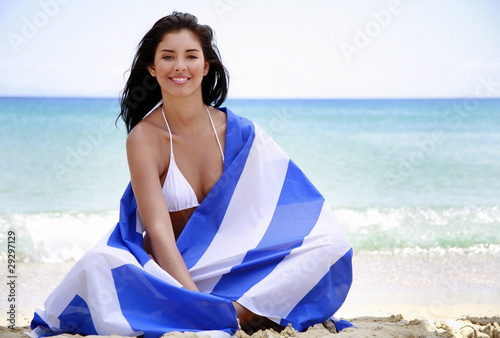 Young woman on beach wrapped in Greek flag