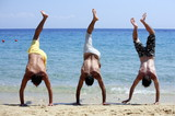 Three young men doing handstands on beach