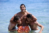Man with two friends in a headlock in water