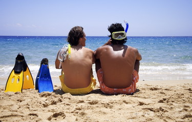 Two men with flippers on the beach